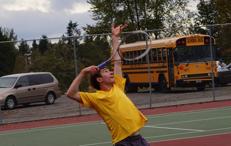 Junior Andrew Szot strikes a quick pose before he serves the ball in his tennis match