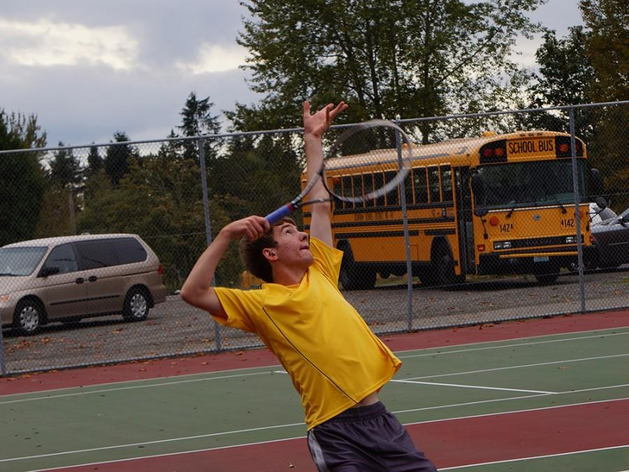 Junior+Andrew+Szot+strikes+a+quick+pose+before+he+serves+the+ball+in+his+tennis+match