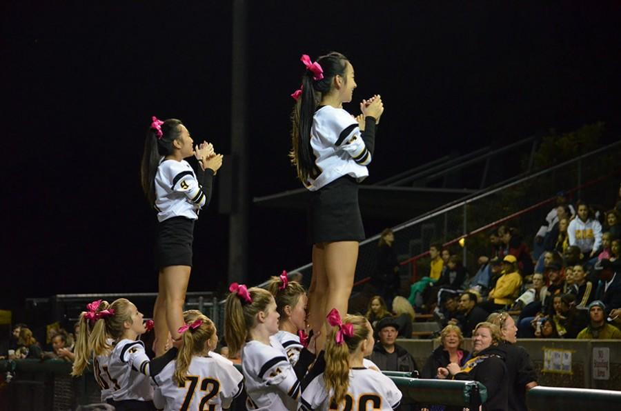 Juniors Ruby Li and Patricia Lee are held in a prep stunt while cheering at the Homecoming game. Cheerleaders practice four hours every week in order to perform at games year round.