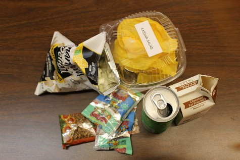 Of all the waste in this photo, only the popcorn and snack wrappers belong in the trash. The food and paper is compostable and the can, milk carton and sandwich box are recyclable. Earth Corps is working hard to educate students on how to sort their food.