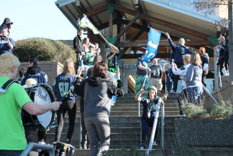 Students parade on the main staircase during the Seahawks assembly on Jan. 30.  The entire event demonstrated the spirit of Inglemoor, as enthusiastic fans dressed up in full blue and green attire and brought flags, hats and jerseys to show their support.  It shows the power of a strong fan-base, a power that will hopefully carry over to the upcoming playoffs in which all five sports could send athletes to state.