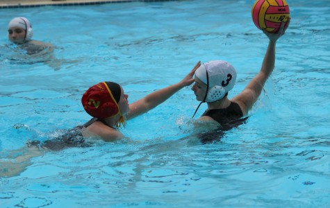Junior Maddie Kutzera, against a Newport High School player, defends the ball as she searches the pool for a team member who would receive the pass.