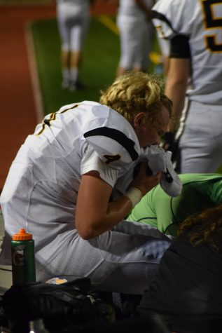 Senior quarterback Brayden Mills sits on the sideline after breaking his fibula and dislocating his ankle during the Vikings game at Lake Washington on Sept. 9. The team has had many injuries this season and hopes that they can succeed despite these setbacks. Inglemoor went on to lose the game 31-21.