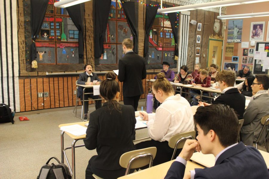 Defense attorney Jack Larsen conducts direct examination on defense witness John Altgeld, portrayed by Hyo Jinn Choe.