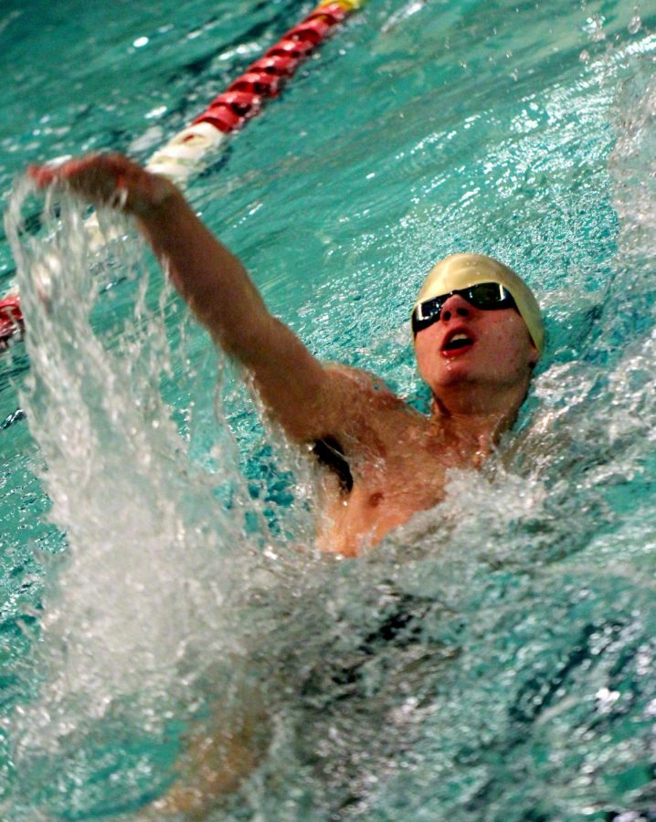 Freshman Andrew James powers through the second half of the 100 backstroke.
