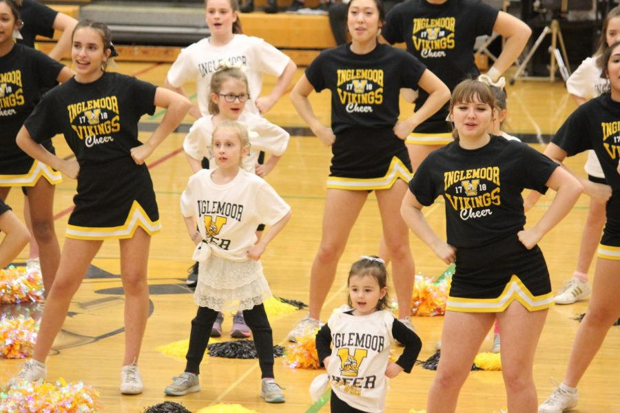 The Lil' Viks perform during halftime at a girls basketball game. They paired up with a chearleader as they practiced their routine.