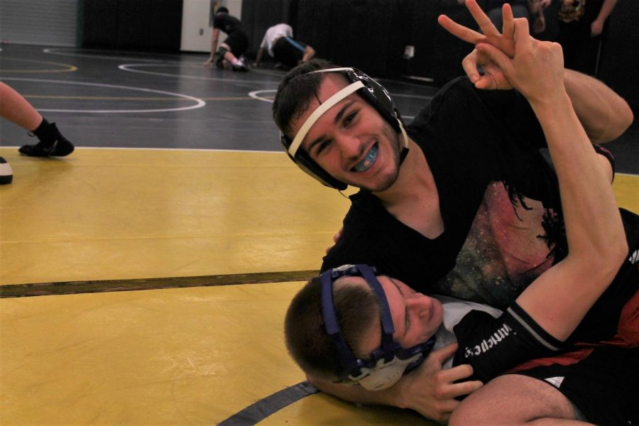 Helsley smiles for the camera mid-hold at wrestling practice. Helsley said that wrestling helped him expand beyond his normal fighting style.