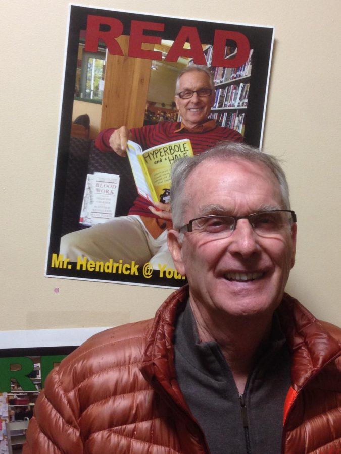 Substitute teacher Dan Hendrick stands under his portrait in the library. Although initially hesitant about teaching the IB Computer Science class in 2005, he can now be found on campus subbing for any and all subjects.