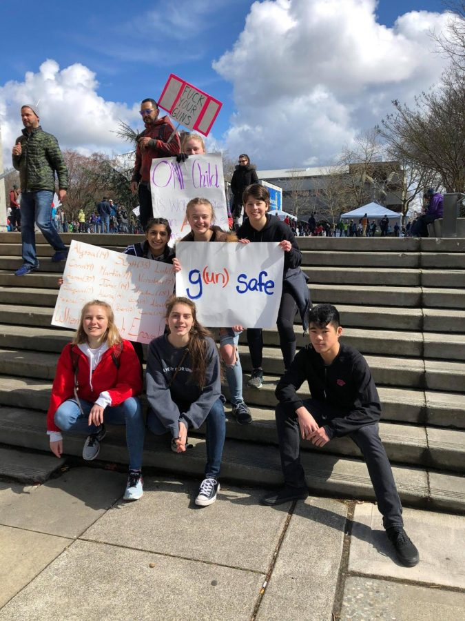 Counterclockwise from bottom left: Hannah Jensen, Nicole Turtle, Justice Maeda, Rachel Lawson, Erin von Steiger, Anisha Chowdry and Emily Bass hold their signs at the Seattle March For Our Lives.