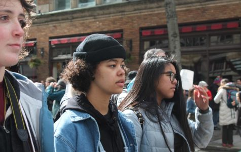 Bailey Johnston, Jocelyn Ayenew and Jed Go march through the street holding cameras and observing the signs of other marchers.
