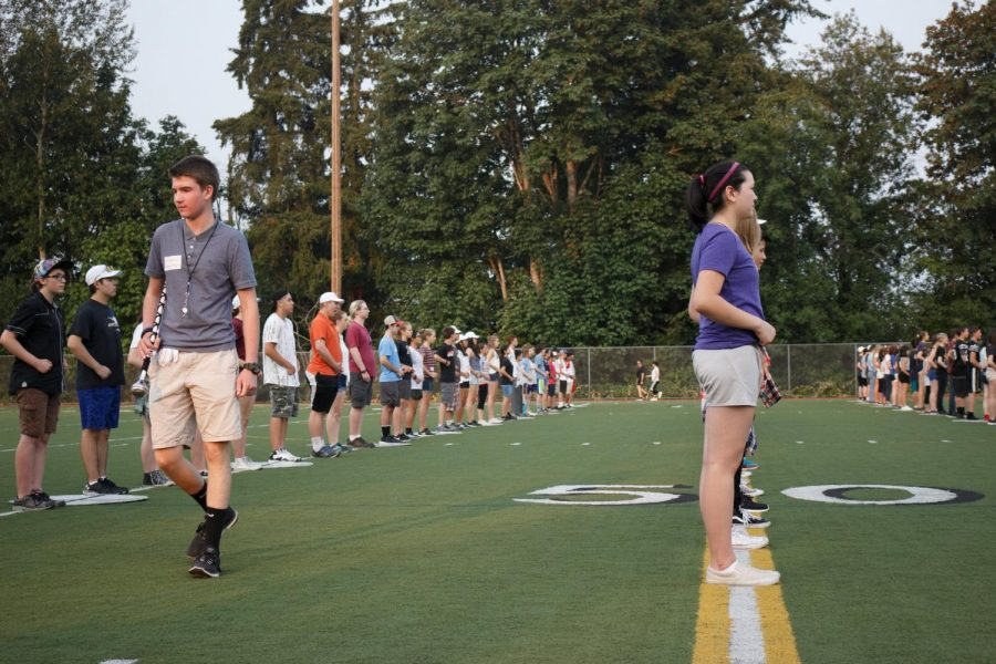 During drill downs, junior drum major Nathan Loutsis (left) makes his way around the lines of students to make sure everyone is coordinated.