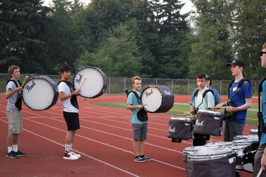 Freshman Amory Wegner, freshman Roman Mar, freshman Luke Knight, sophomore Christopher Willis and senior Gavin Wright practice within their drumline section. During the school year, time is broken up into class time and rehearsals, Wright said. But when we have a big chunk of 6 hours like this, people are more focused and try to get something done.