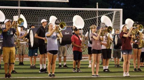 In the front row, senior Berk Uzuncaova plays mellophone and senior Hannah Wiggins, freshman Holland Stuart and junior Chloe Person play baritone during a practice runthrough of the Inglemoor Fight Song, a favorite amongst students at football games.