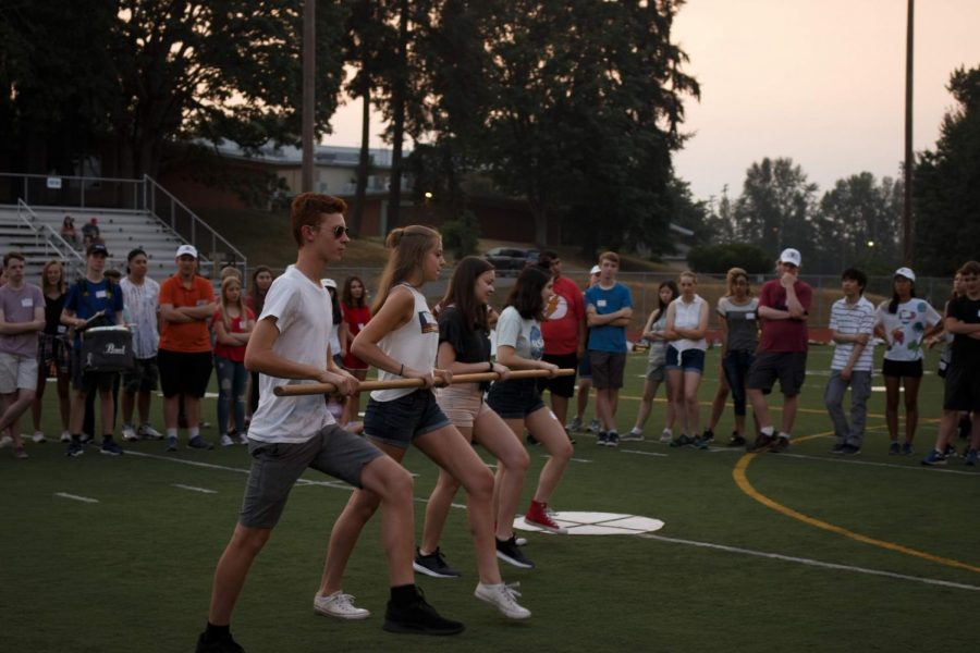 Junior Peter Lie, junior Eva Taylor, senior Claire Werner and senior Ruby Leotta demonstrate the pinwheel in front of the other students. The pinwheel is a formation that moves the band between vertical and horizontal positions on the field. Each squad (a group of 4 students) will pivot around a central point to move along a quarter circle path.