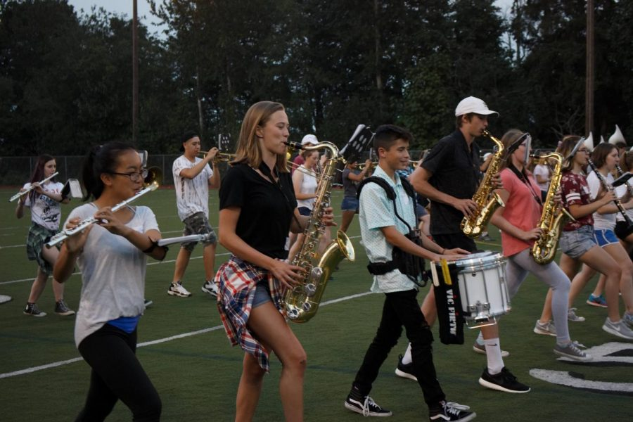 Freshman Jaclyn Woo, sophomore Ellie Pratt, sophomore Christopher Willis and sophomore Gavin Hudkins practice marching with their instruments.