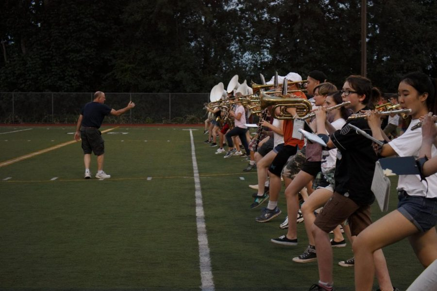 Band instructor Bruce Wilson motions the band to move forward as they practice marching through the general layout of a football game.