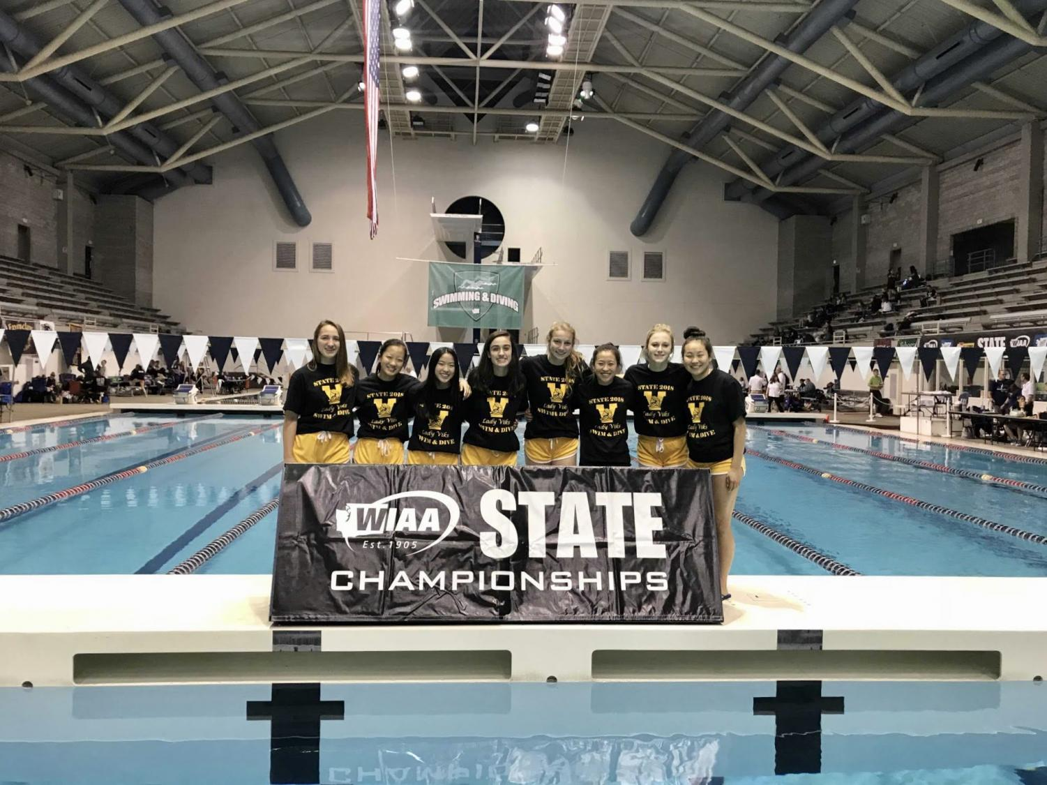 From left to right, freshman Madelyn Brown, freshman Grace Liu, freshman Jewel Hau, senior Julia Pakkala, freshman Naomi Voeller, freshman Megan Chow, sophomore Ella Marzec and junior Maddy Chow pose in front of the state championships banner prior to swimming at the preliminaries on Nov. 9.