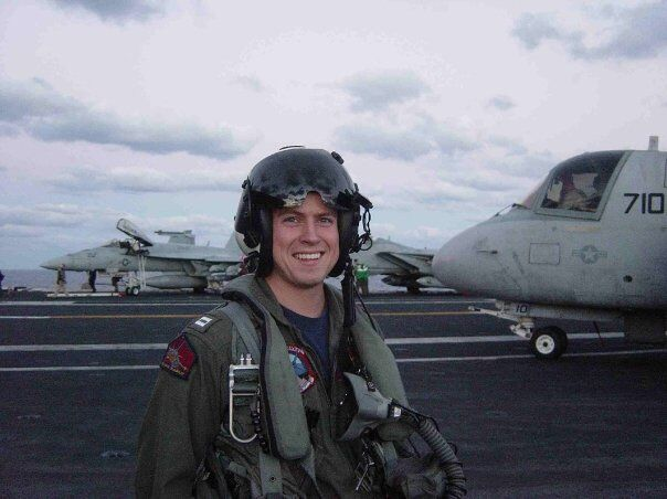 Patrick Myrick stands in front of a jet in his flight gear.