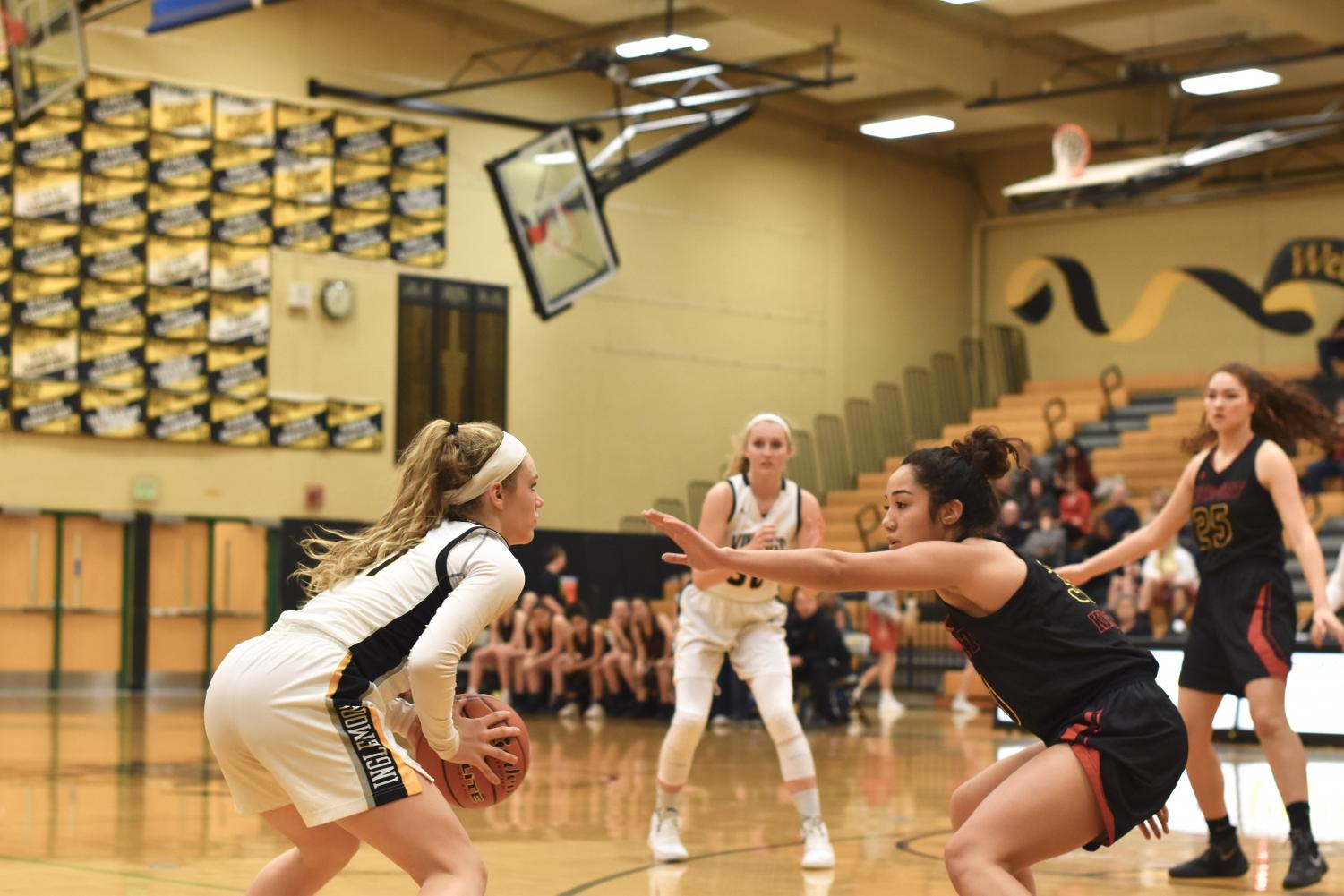 Junior Lucy Young faces a Newport defender as she scans the court for an open teammate. The team would go on to win with a score of 57-48.