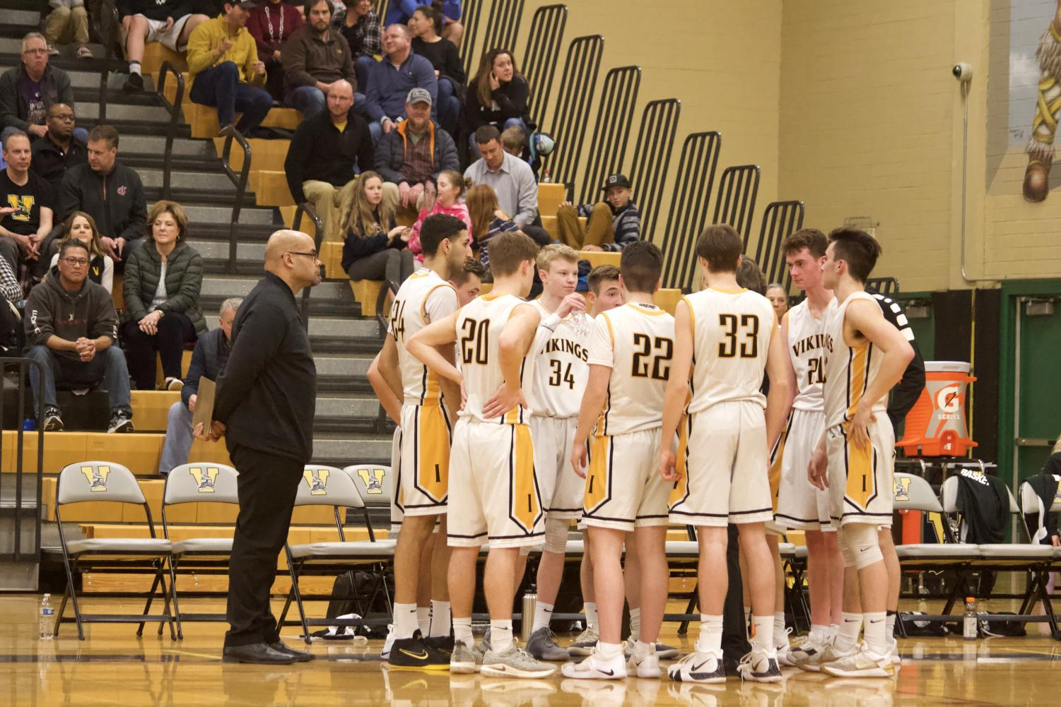 The team huddles around head coach Gregory Lowell in the final seconds of their 68-67 win against Bothell High School.