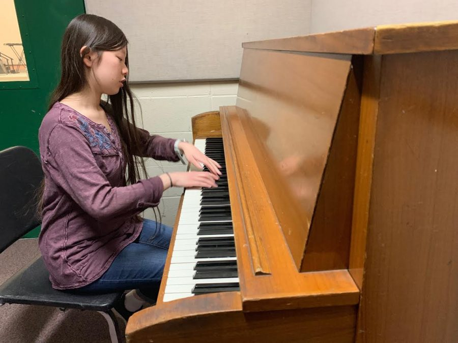 Junior Jenny Xiong warms up as she plays the piano in a practice room.
