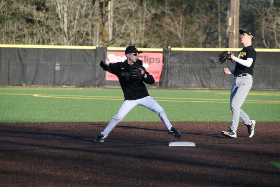 Freshman Cameron Hughes pitches the ball to his teammates in preparation for their first game of the season against Juanita High School on Tuesday, March 12.