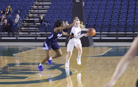 Junior Lucy Young dribbles up the court through a Rogers defender in round one of state. The Vikings advanced with a 65-54 overtime victory.