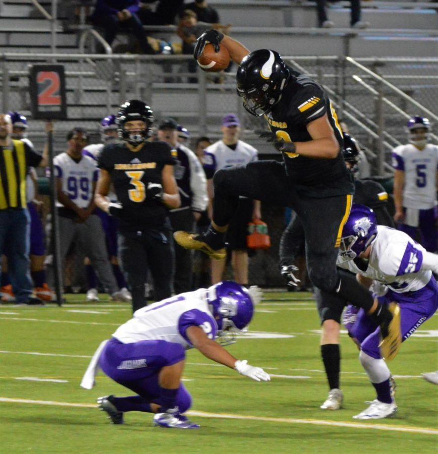 "Quentin Moore jumps over another player at the 2018 homecoming game against North Creek. Moore described this moment as ""his favorite highlight of the season."""