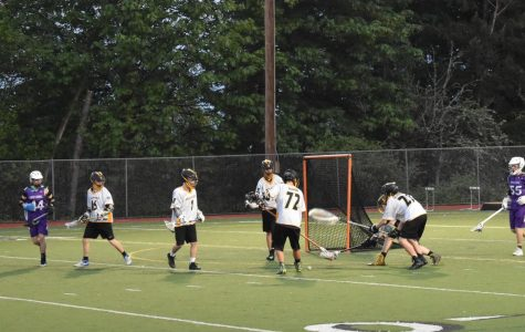 Vikings lacrosse players recover the ball at a game against North Creek High School.