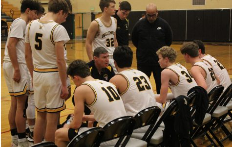 The boys varsity team huddles to listen to Coach Greg Lowell halfway into the game. The team beat Juanita 67-46 on Saturday, Dec. 7. Photo by Caden Pavlovski