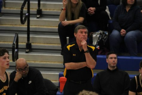Coach Greg Lowell observes varsity players during game against Bothell on Friday, Jan. 31. Sitting behind him on the left is coach Mitchell Blackburn and on the right is coach Collin Portugal. Photo by Ella Barnard